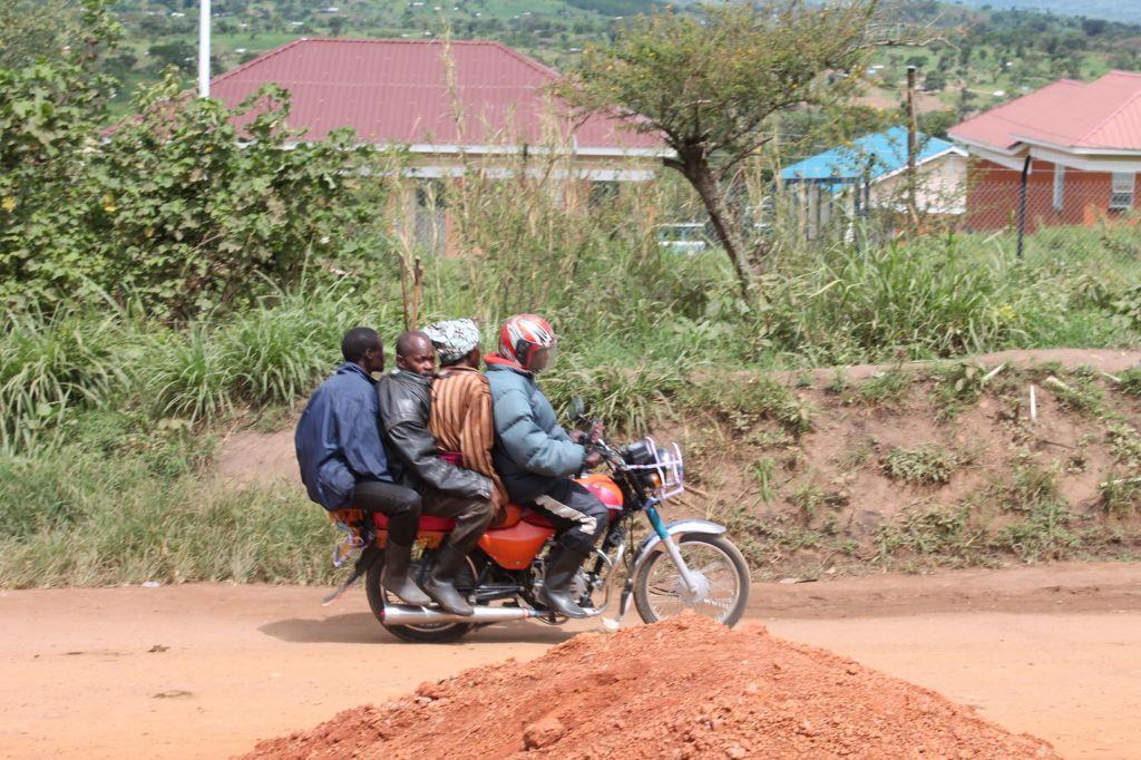 Neljä afrikkalaista miestä matkalla moottoripyörän selässä