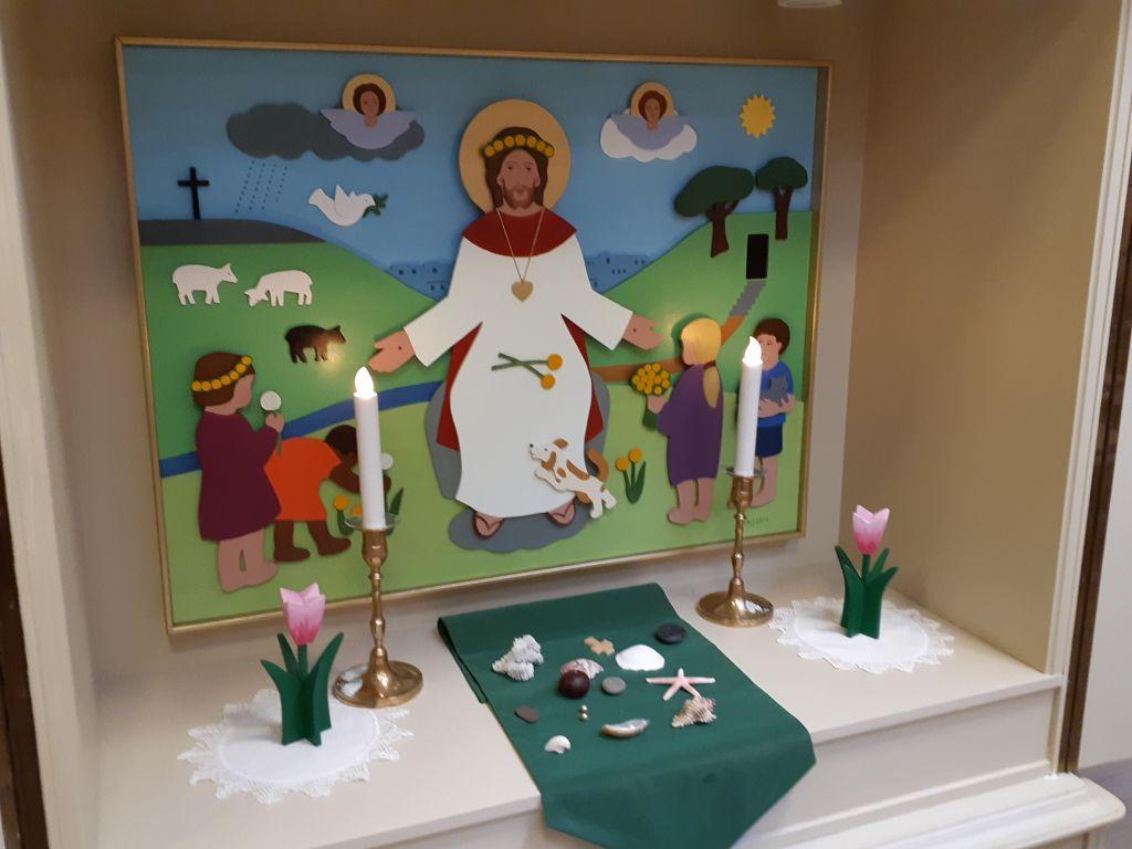 Jeesus siunaa lapsia-alttaritaulu, -kynttilät ja kukat.