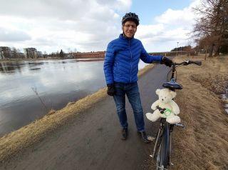Piispa Jukka Keskitalo polkupyörän kanssa, jonka tarakalla on nalle