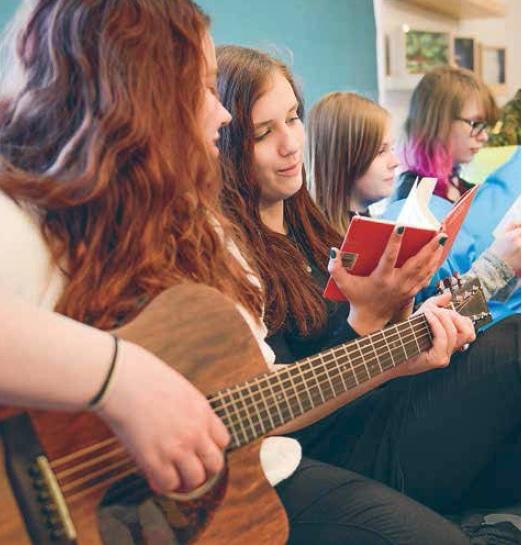 Kuva: Kirkon kuvapankki, kuvaaja Suvi Pietilä. Rippikoulussa lauletaan, yksi nuorista soittaa kitaraa.